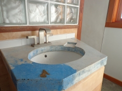 Small bathroom concrete countertop with moulded soap-dish and undermount sink